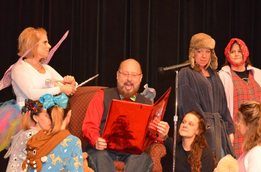 High School principal Mr. Tom Yoder does his rendition of 'Twas the Night Before Christmas with members of the faculty and staff.