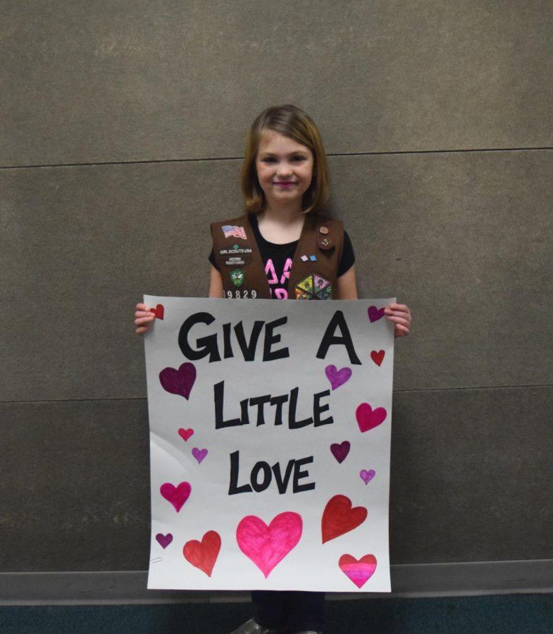 Third grader Emma Ellenberger holding a sign for the