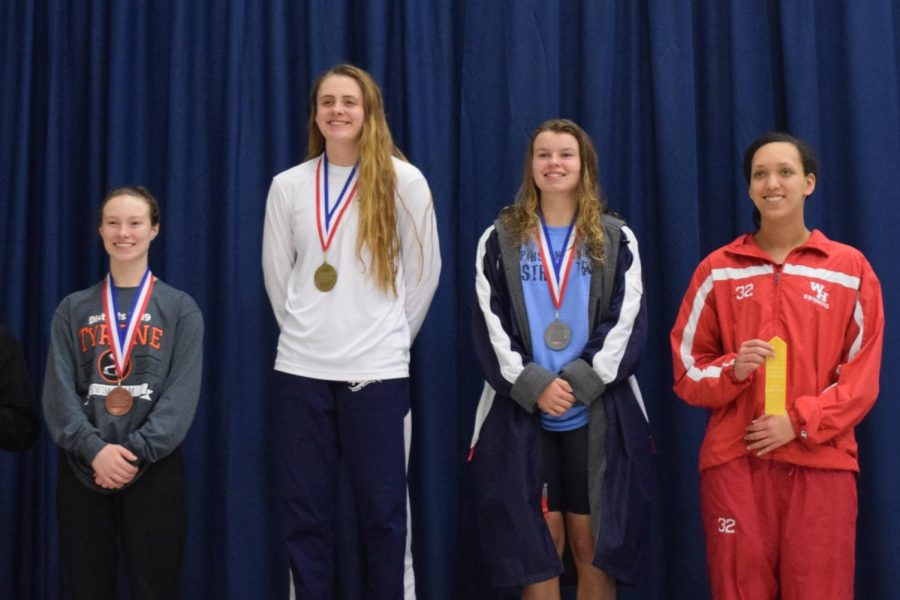 Sophomore+Maddie+Coleman+smiling+proudly+with+her+bronze+medal+from+the+D6+District+Championship+meet.