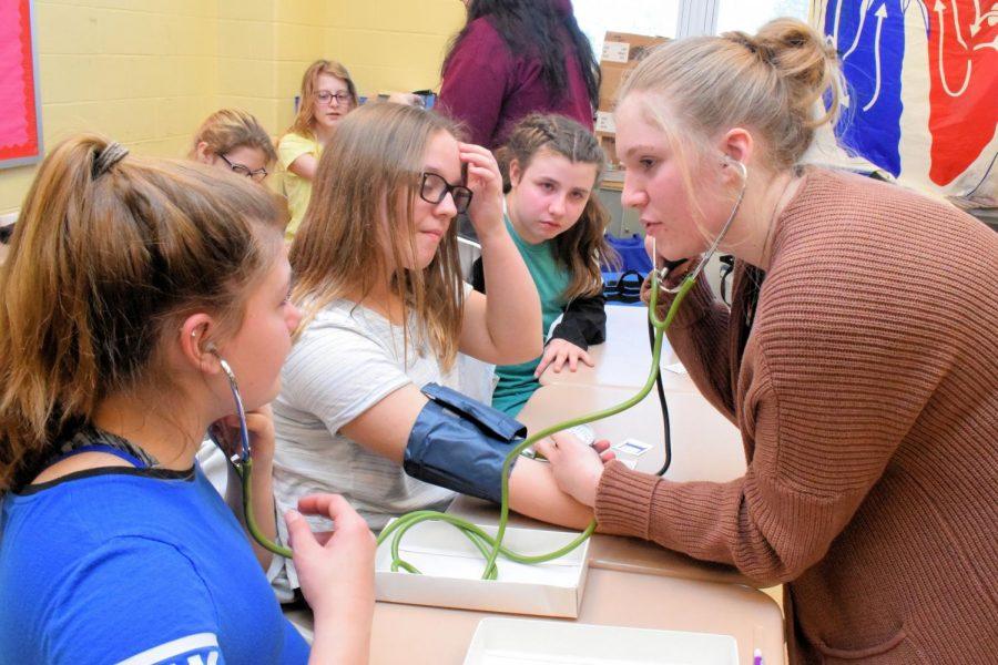 Sixth graders Layna Dibert, Jenna Kerr, Naveah Conte, learn how to take blood pressure from sophomore Hollie Keller.