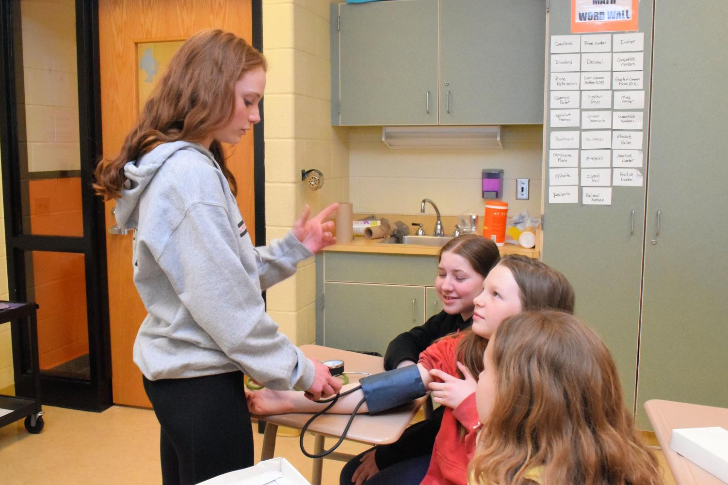 Sophomore+Ella+Pearson+works+with+sixth+graders+Alexis+Boozer%2C+Kendra+Sweeney%2C+and+Lily+Eckley%2C+explaining+how+the+blood+pressure+cuff+and+stethoscope+work.%0A