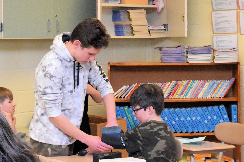 Sophomore+Cameron+Vincent+puts+the+blood+pressure+cuff+on+sixth+grader+Teagan+Beeler.