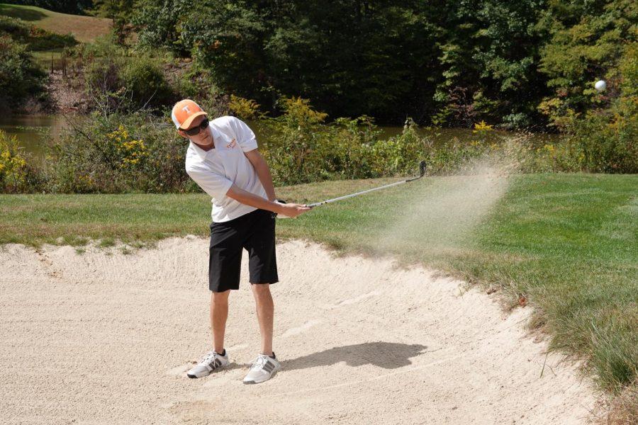 Senior Trey Kyle hitting a bunker shot onto the green.