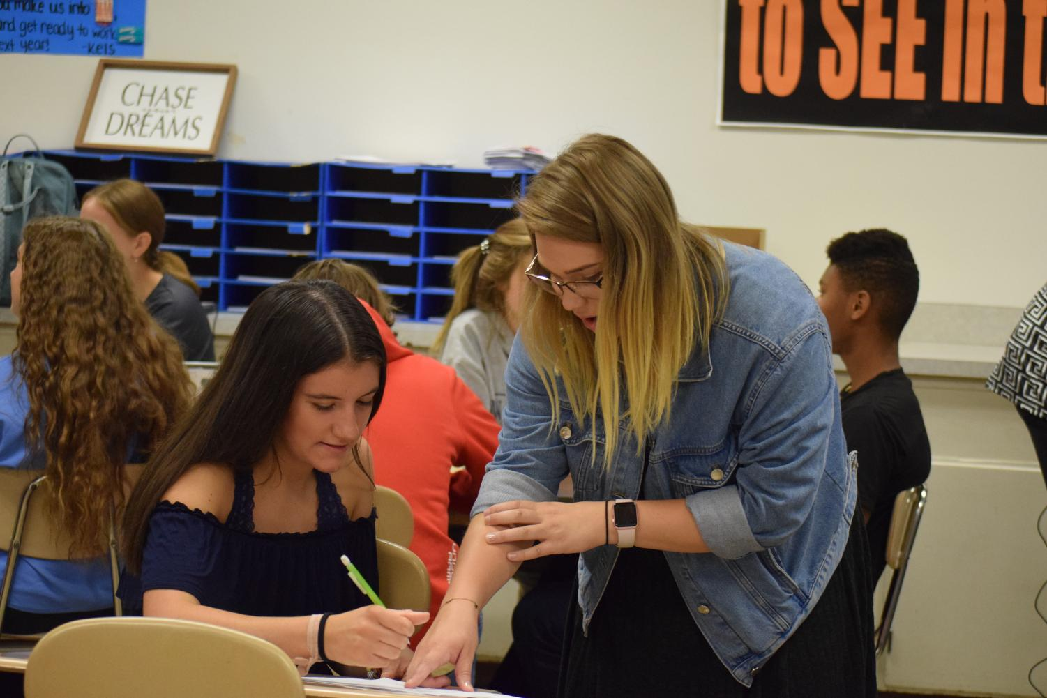 Miss Rayne Young is the math Americorps teacher  for the 2019-2020 school year.  Here she helps junior Mattie Cherry.