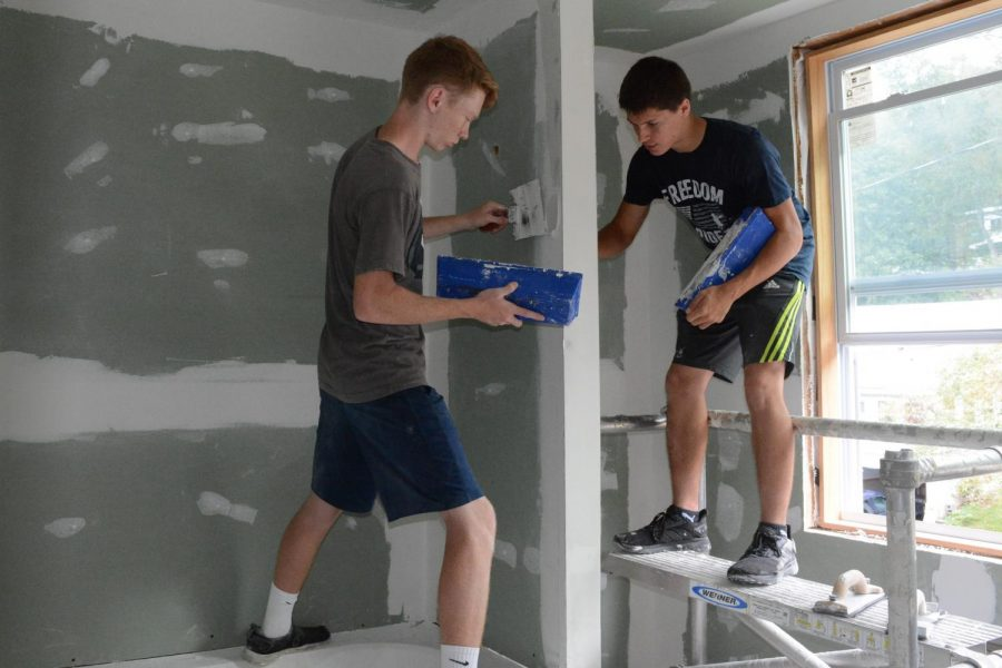 Seniors Zack Neff and Isaac Parks working on finishing the drywall