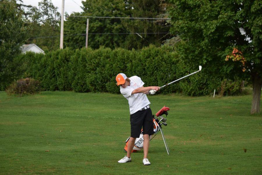 Brent McNeel hitting his iron on the fairway.