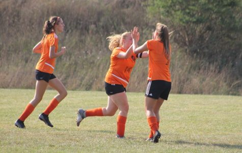 Kendall Markley, Chloe LaRosa, and Sophia Nelson celebrating after a goal.