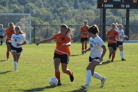 Freshman Chloe LaRosa dribbling the ball away from a Penns Valley defender.
