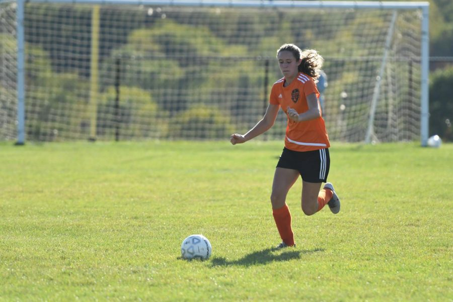 Natalie Saltsgiver dribbling the ball up the field.