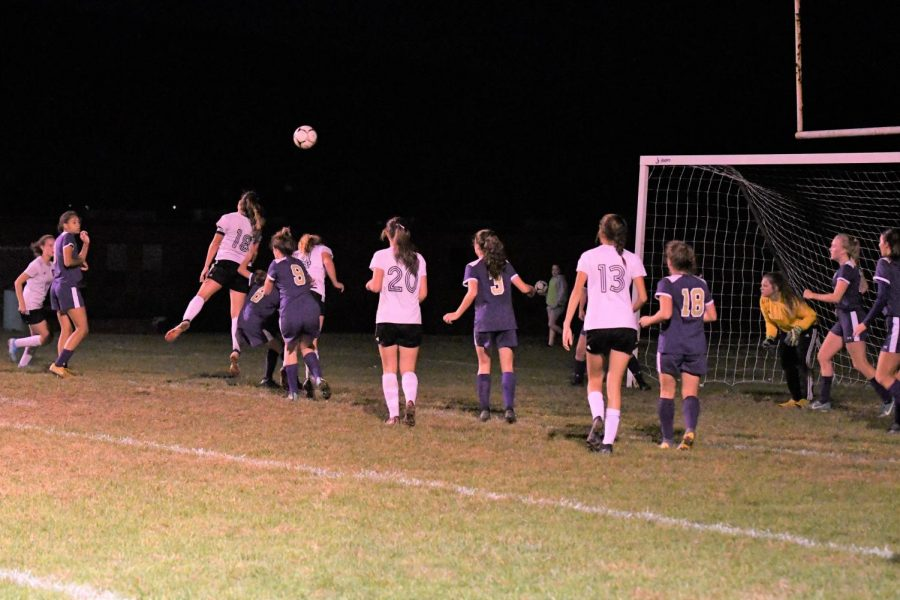 Lindsey Parks heading the ball towards the goal during a corner kick.