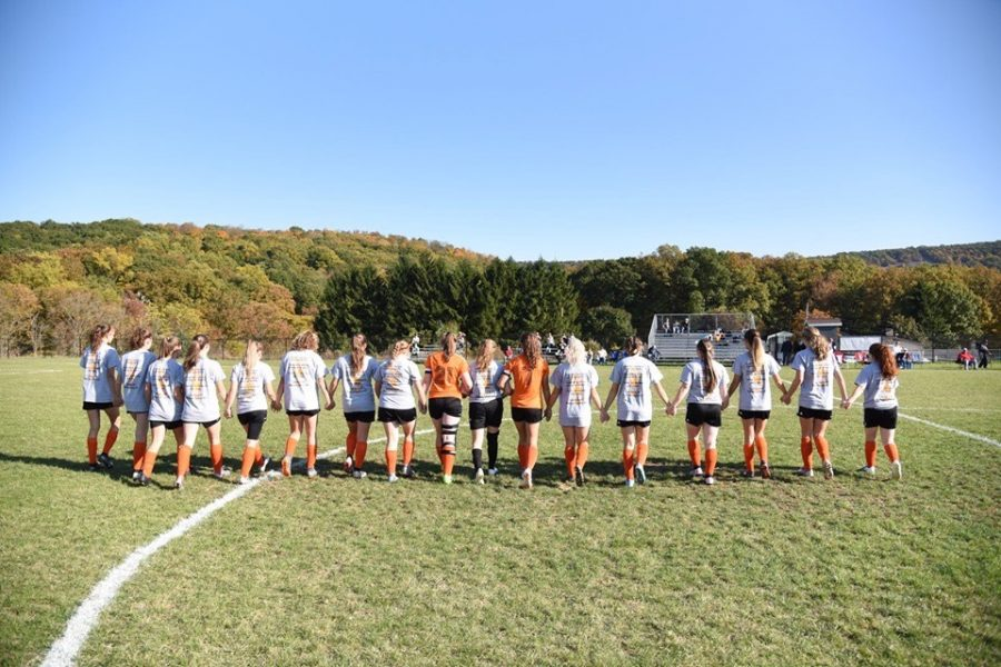 The girls varsity soccer team walking across the soccer field hand-in-hand.