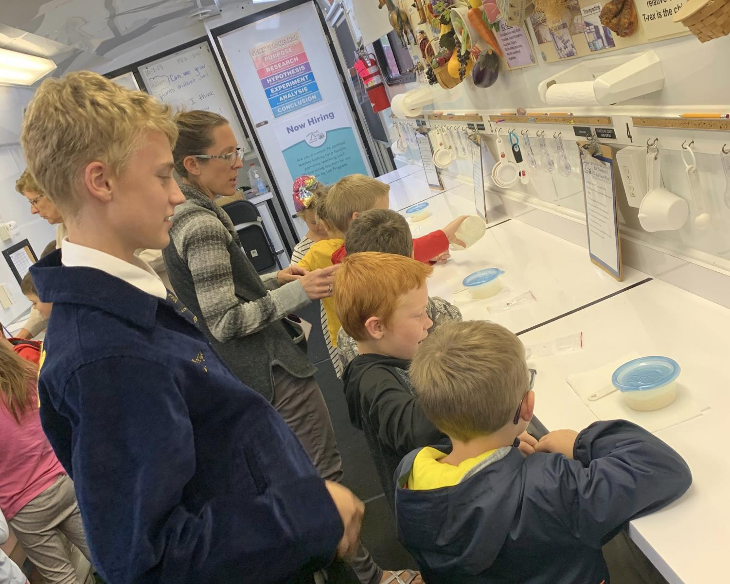 First-year FFA member, Justin Jackson helps elementary students with their experiment called