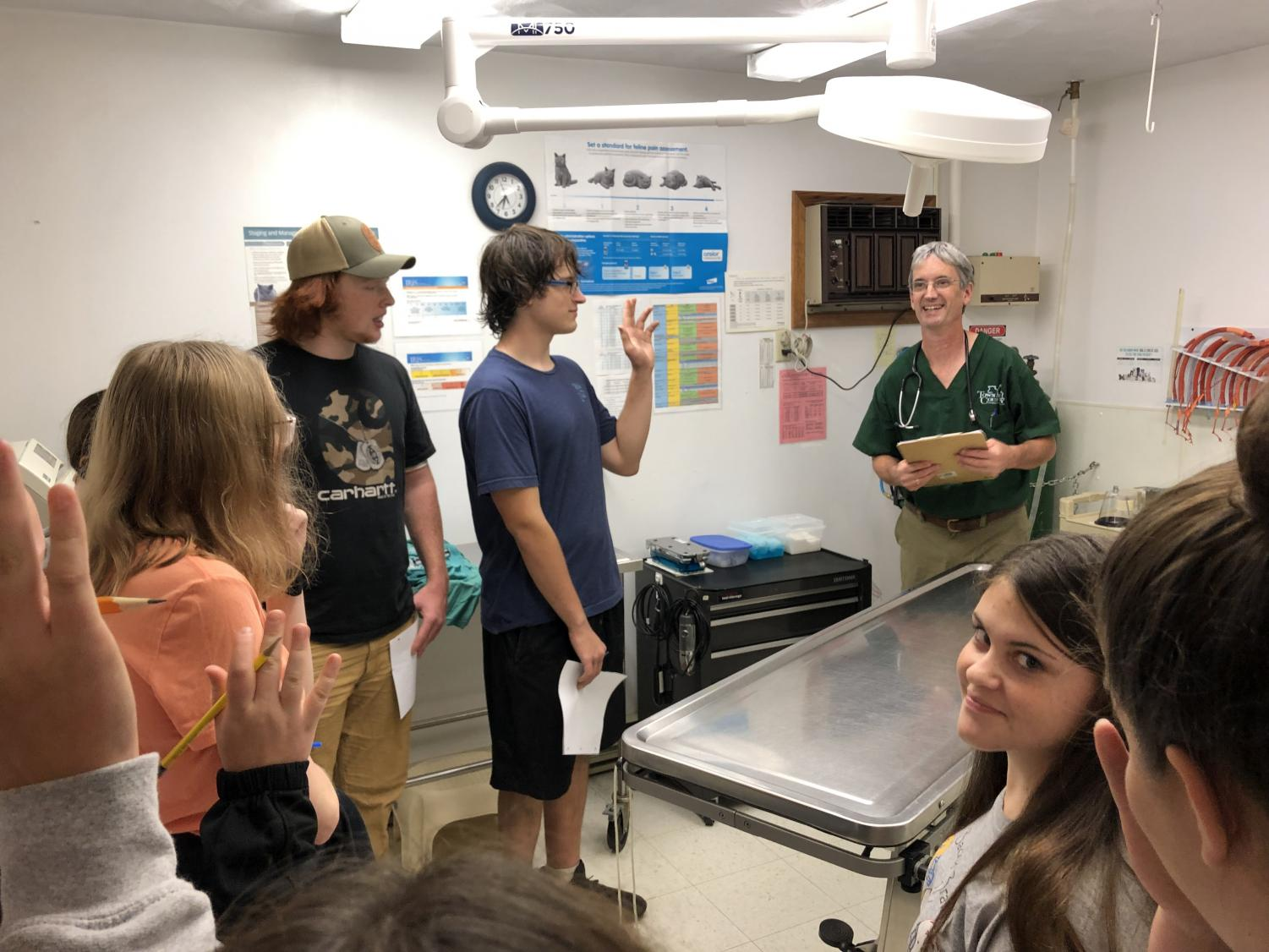 FFA member Brody Rizzo raises his hand to answer questions from Dr. Aquadro (right) during the tour of the exam room at Town and Country Animal Hospital in Warriors Mark