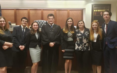 The Mock Trial B Team gets a photo with the judge after their trial.