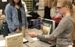 Junior Libby Buck assists Stem AG participant, Nora Hoy, with her Goldberg Machine.