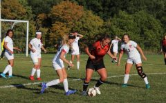 Chloe LaRosa taking a touch on the ball before crossing it to an open player.