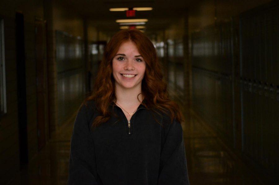 Rylee Fleck smiling in a dark hallway.
