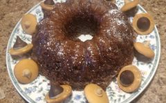 A sugar coated acorn bundt cake with in a wreath of acorn cookies.