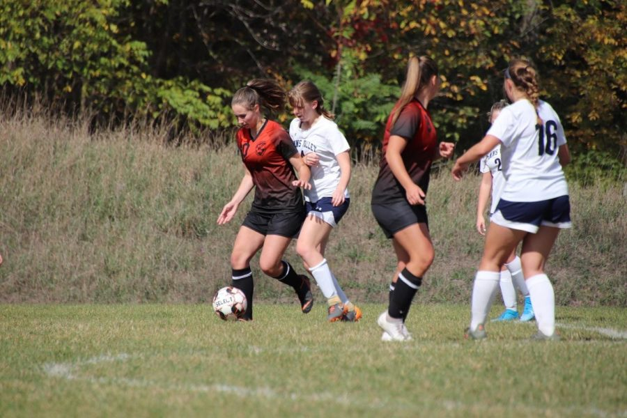 Sophomore Eliza Vance using her body to guard the ball and look for an open pass upfield.
