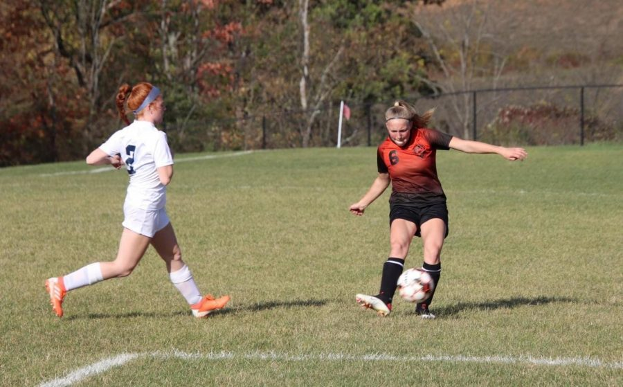 Junior Mackenzie Latchford shoots the ball up-field and away from the opposing team.