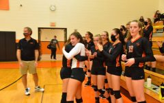 Bauer receives congratulations from senior teammate Mattie Cherry and the rest of the Tyrone varsity squad after recording her 500th kill.
