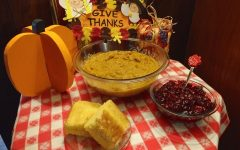 A plate of cut cornbread, a bowl of cranberry sauce and a floral decorated bowl of butternut squash decorated appropriate to the season.
