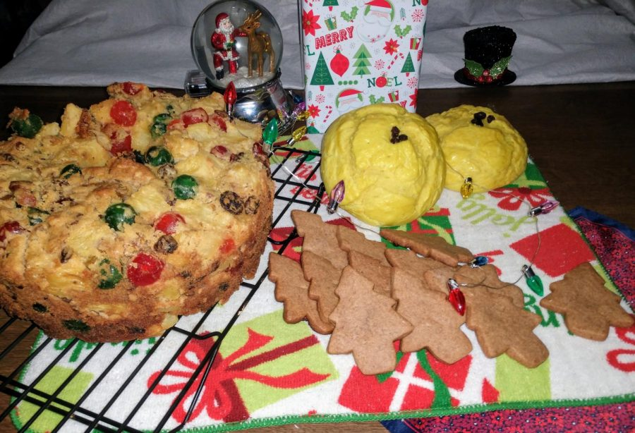 A+festive+fruitcake+cooling+on+a+rack+beside+a+dozen+Speculaas+trees+pointed+towards+a+pair+of+yellowed+Lussekater+buns+adorn+in+lights+representative+of+the+holiday+season.