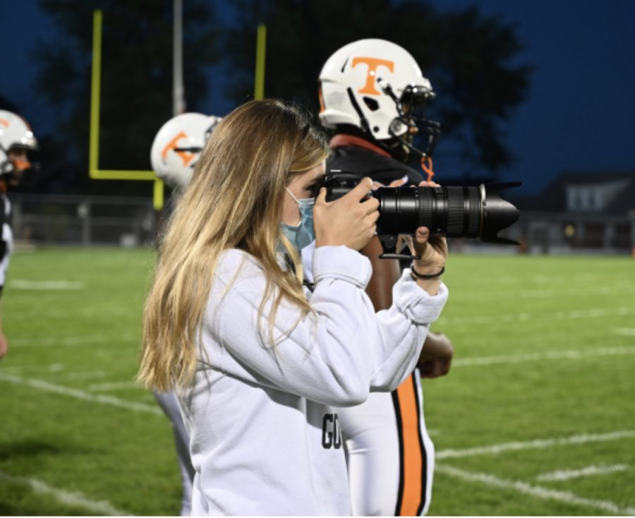 Lucia pointing her camera to the field to capture a play during a TAHS football game