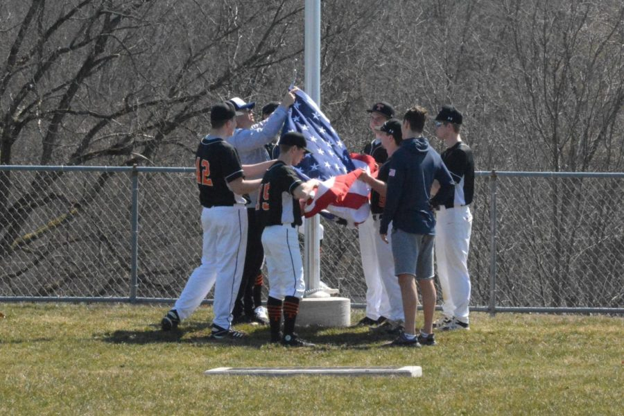 TAHS senior baseball players raise the flag at the flagpole honoring their friend and teammate Adam Fink.