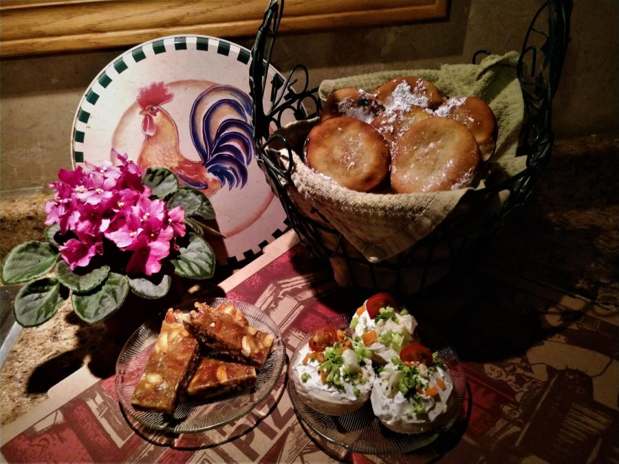 A beignet basket towering above a colourful display of turron slices and bite-sized vegetable pizzas.