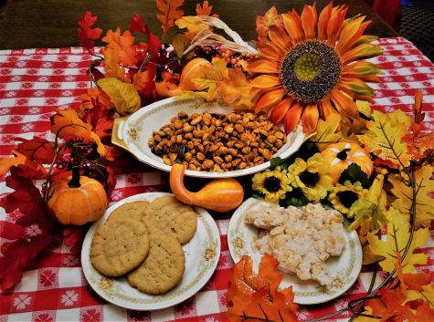 A bowl of honey roasted peanuts preceding plates of peanut butter cookies and peanut brittle enwreathed in seasonal flora.
