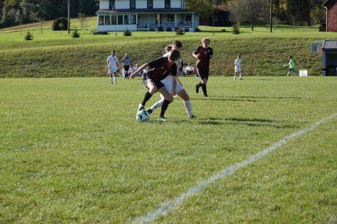 Conner Bardell dribbling the ball away from an opposing defender.