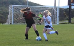 Junior Eliza Vance taking the ball away from the opposing player.